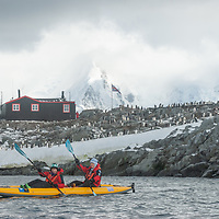 Kayakers paddle near Port Lockroy Museum on Goudier Island, near the Antarctic Peninsula, Antarctica. Mountains on Anvers Island are in the background. in the background.