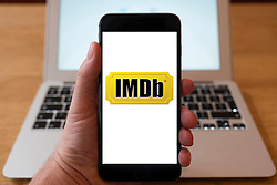 Using iPhone smartphone to display logo of IMDB, Internet Movie Database, website for movie industry