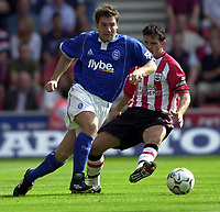 Photo: Richard Lane.<br />Southampton v Birmighma City. Barclaycard Premiership.<br />23/08/2003.<br />David Dunn offloads the ball as Jason Dodd moves in.