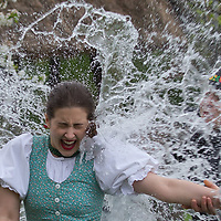 Girl wearing traditional dress is targeted by buckets of water splashed on her as part of the fertility traditions during the Easter watering celebration in the Skansen open air ethnographic museum in Szenna (about 200 km South-West of capital city Budapest), Hungary on April 14, 2017. ATTILA VOLGYI