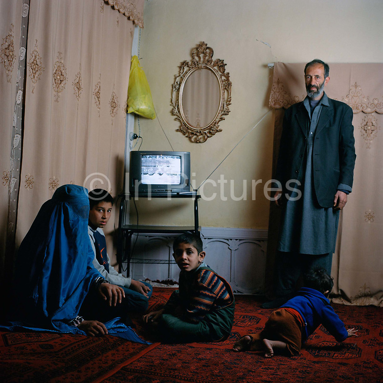 """Zulgai, a furniture maker at home with his family. """"The children watch cartoons ,I like serious programs, like the news and my wife prefers to watch a Chinese soap that deals with the  unhappy life of a royal daughter."""""""