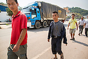 13 MARCH 2013 - ALONG HIGHWAY 13, LAOS: A truck headed into China passes Chinese man walking along the highway near the end of Highway 13 in the Boten Special Economic Zone. The SEZ is in Laos immediately south of the Lao Chinese border. It has turned into a Chinese enclave but many of the businesses struggle because their goods are too expensive for local Lao to purchase. Some of the hotels and casinos in the area have been forced to close by the Chinese government after reports of rigged games. The paving of Highway 13 from Vientiane to near the Chinese border has changed the way of life in rural Laos. Villagers near Luang Prabang used to have to take unreliable boats that took three hours round trip to get from the homes to the tourist center of Luang Prabang, now they take a 40 minute round trip bus ride. North of Luang Prabang, paving the highway has been an opportunity for China to use Laos as a transshipping point. Chinese merchandise now goes through Laos to Thailand where it's put on Thai trains and taken to the deep water port east of Bangkok. The Chinese have also expanded their economic empire into Laos. Chinese hotels and businesses are common in northern Laos and in some cities, like Oudomxay, are now up to 40% percent. As the roads are paved, more people move away from their traditional homes in the mountains of Laos and crowd the side of the road living off tourists' and truck drivers.    PHOTO BY JACK KURTZ