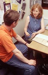 Female teacher sitting at desk talking to student,