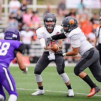 Quaterback for the Aztec Tigers Zach Taylor hands the ball off as Adam Rodriguez of Miyamura approaches, Friday August, 24, 2018 at Angelo DiPaolo Stadium in Gallup.
