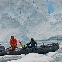 A SCUBA diver re-boards a Zodiac raft after photographing below a calving glcier cliff at Neko Harbor, Antarctica.