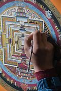 Nepal, Kathmandu, Thangka a Tibetan Buddhist religious painting, with a painter's hand holding a brush