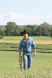 cowboy walking through a pasture on a ranch