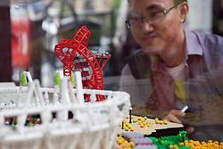 © Licensed to London News Pictures. 05/07/2012. London, UK. A man gazes at a minature replica of the Olympic Park constructed from Lego. LEGO creator, Warren Elsmore used around 250,000 standard LEGO bricks to create a miniature replica of the London 2012 Olympic Games Park. The model took Warren, aged 35 from Edinburgh, 300 hours to construct and is on display at the 'Visit Denmark' Olympic Village  at St Katharine Docks, London. Photo credit : Vickie Flores/LNP
