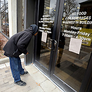 """Vincent Parcher reads a flyer taped to the door of Toledo Municipal Court before he enters the courthouse in Toledo on Thursday, March 12, 2020. The flyer states that in accordance with Ohio Gov. Mike DeWine's recent executive order in response to coronavirus, the court is """"implementing efforts in social distancing."""" Among these efforts is extending the due date for fines, fees and costs that are due between March 11 and June 1 an additional 90 days from the original due date. THE BLADE/KURT STEISS <br /> CTY virus13"""