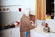 Elderly woman at kitchen sink at home 1970s British way of life