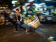 "21 DECEMBER 2015 - BANGKOK, THAILAND:  A porter hauls a load to a waiting taxi from Pak Khlong Talat, also called the Flower Market. The market has been a Bangkok landmark for more than 50 years and is the largest wholesale flower market in Bangkok. A recent renovation resulted in many stalls being closed to make room for chain restaurants to attract tourists. Now Bangkok city officials are threatening to evict sidewalk vendors who line the outside of the market. Evicting the sidewalk vendors is a part of a citywide effort to ""clean up"" Bangkok.      PHOTO BY JACK KURTZ"