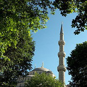 Perspective Blue mosque's minaret from outside garden