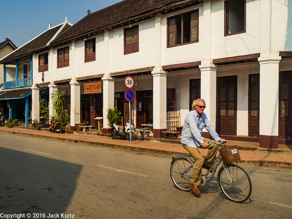 """13 MARCH 2016 - LUANG PRABANG, LAOS:  A tourist peddles past a French colonial house that has been turned into a spa in Luang Prabang. Luang Prabang was named a UNESCO World Heritage Site in 1995. The move saved the city's colonial architecture but the explosion of mass tourism has taken a toll on the city's soul. According to one recent study, a small plot of land that sold for $8,000 three years ago now goes for $120,000. Many longtime residents are selling their homes and moving to small developments around the city. The old homes are then converted to guesthouses, restaurants and spas. The city is famous for the morning """"tak bat,"""" or monks' morning alms rounds. Every morning hundreds of Buddhist monks come out before dawn and walk in a silent procession through the city accepting alms from residents. Now, most of the people presenting alms to the monks are tourists, since so many Lao people have moved outside of the city center. About 50,000 people are thought to live in the Luang Prabang area, the city received more than 530,000 tourists in 2014.   PHOTO BY JACK KURTZ"""