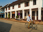 "13 MARCH 2016 - LUANG PRABANG, LAOS:  A tourist peddles past a French colonial house that has been turned into a spa in Luang Prabang. Luang Prabang was named a UNESCO World Heritage Site in 1995. The move saved the city's colonial architecture but the explosion of mass tourism has taken a toll on the city's soul. According to one recent study, a small plot of land that sold for $8,000 three years ago now goes for $120,000. Many longtime residents are selling their homes and moving to small developments around the city. The old homes are then converted to guesthouses, restaurants and spas. The city is famous for the morning ""tak bat,"" or monks' morning alms rounds. Every morning hundreds of Buddhist monks come out before dawn and walk in a silent procession through the city accepting alms from residents. Now, most of the people presenting alms to the monks are tourists, since so many Lao people have moved outside of the city center. About 50,000 people are thought to live in the Luang Prabang area, the city received more than 530,000 tourists in 2014.   PHOTO BY JACK KURTZ"