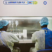 INDIVIDUAL(S) PHOTOGRAPHED: N/A. LOCATION: St. Damien Hospital, Nos Petits Frères et Sœurs, Tabarre 41 Commune, Haïti. CAPTION: Two laboratory employees at St. Damien Hospital sit at a laminar flow workstation, preparing medicines.