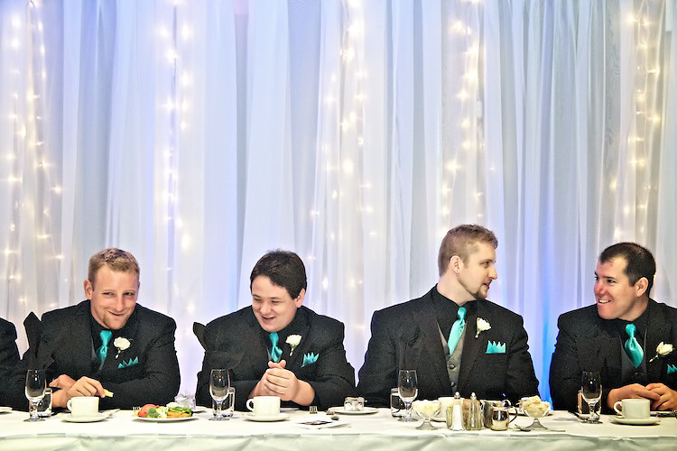 The groomsmen chat during the wedding reception dinner. Behind the head table are strings of lights behind curtains. <br /> <br /> To view Katie and Brad's complete Wedding Gallery Collection, visit the Client Area and log-in. You'll be able to view all images as a slideshow, order prints and more.<br /> <br /> © Images of a Promise by Dean Oros Photo + Design