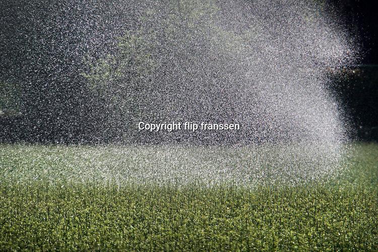 Nederland, Groesbeek, 24-2-2020 Een boer beregent zijn akker nat dmv een waterkanon. Het water wordt uit een put in de grond opgepompt en is dus grondwater. Waterdruppels in waterscherm .Foto: Flip Franssen
