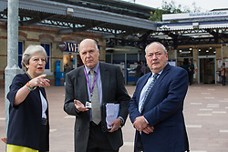 Maidenhead, UK. 11th October, 2021. Theresa May, Conservative MP for Maidenhead, speaks to Cllr Gerry Clark (c), the Royal Borough of Windsor and Maidenhead's cabinet member for transport and infrastructure, and Bob Beveridge (r), chair of the Thames Valley Berkshire LEP, on the occasion of the official opening of a new station forecourt. The £3.75m refurbishment is intended to make the area around the station more commuter-friendly in anticipation of an increase in passengers when Crossrail opens and to improve both the interchange between trains and other forms of transport and walking and cycling links between the station and the town centre.