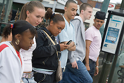 Group of teenagers queuing for a bus,