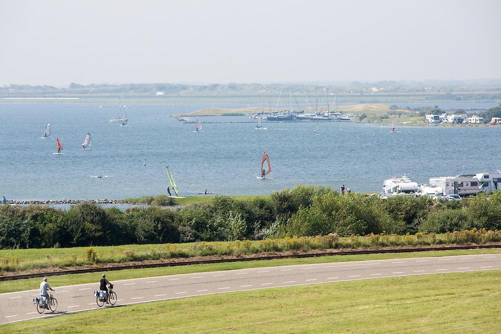 Fietsers rijden voorbij het meer bij de Brouwersdam waar volop gewinsurft wordt.<br /> <br /> Cyclists ride past the lake at the Brouwersdam full of surfers.
