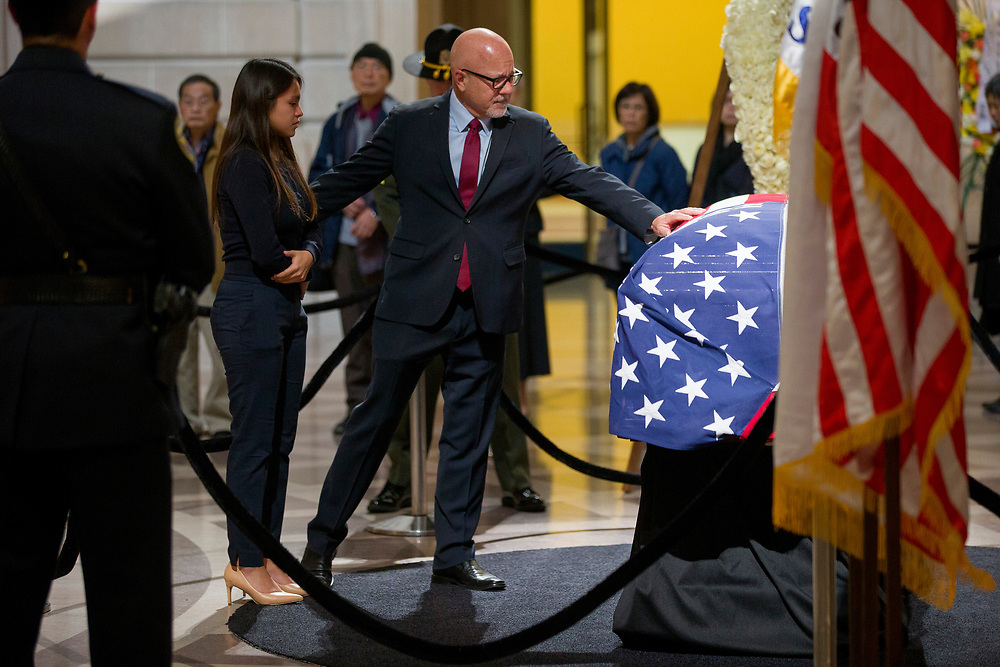 Steve Kawa, who is the former chief of staff for San Francisco Mayor Ed Lee, puts his hand over Lee's casket at City Hall on Friday, Dec. 15, 2017, in San Francisco, Calif. Lee died on Tuesday from a heart attack. He was 65 years old. Kawa is seen with his daughter Katherine.