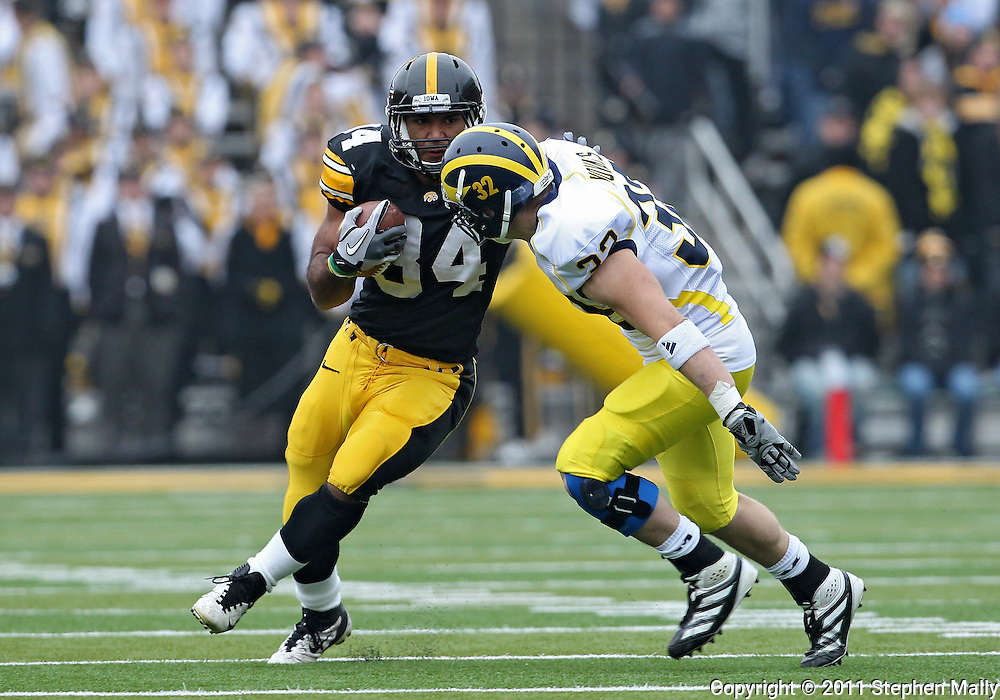 November 05, 2011: Iowa Hawkeyes running back Marcus Coker (34) tries to avoid Michigan Wolverines safety Jordan Kovacs (32) during the first quarter of the NCAA football game between the Michigan Wolverines and the Iowa Hawkeyes at Kinnick Stadium in Iowa City, Iowa on Saturday, November 5, 2011. Iowa defeated Michigan 24-16.