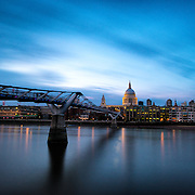 The Thames, with the Millenial Bridge and the dome of St Paul's Cathedral in London at dusk.