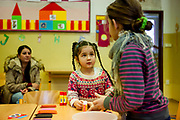 Esther Kroscenova (6) with her mother Daniela Kroscenova (27) in the back waiting for an enrollment examination (test) of daughter Esther who should be a first class pupil in the school year 2016/2017 in a mainstream school in the city of Ostrava, where Roma and non Roma children are educated together. The school is named ZS Chrustova elementary school. The girls are doing some handicraft during waiting for the test. (NO signed MODEL RELEASE for the girl on the right).
