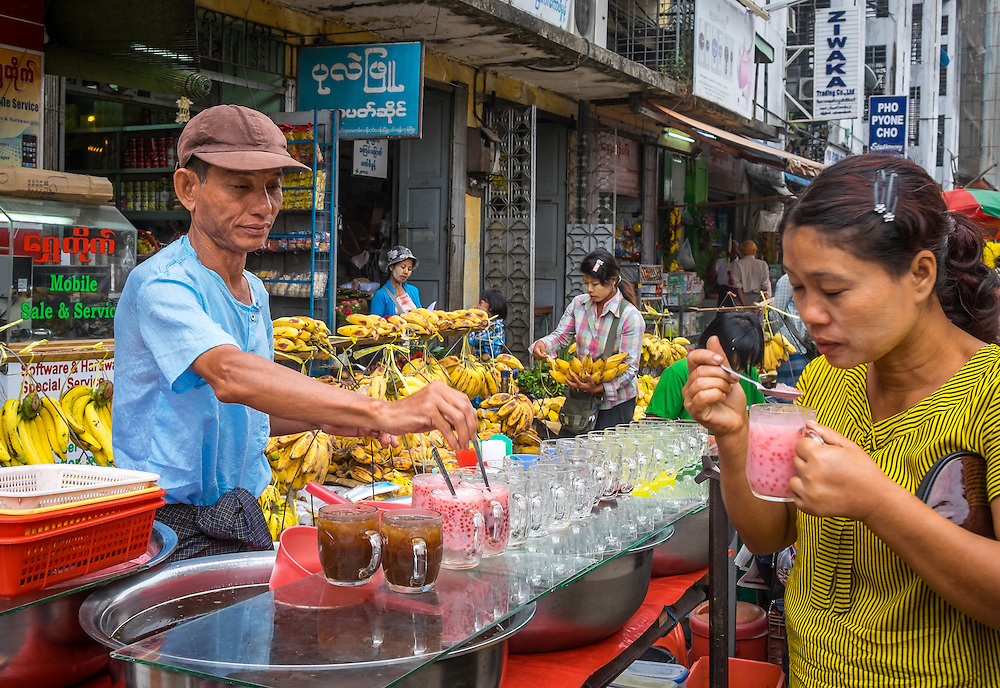 YANGON, MYANMAR - CIRCA DECEMBER 2013: Merchant selling tea and juices in the street market of Yangon.