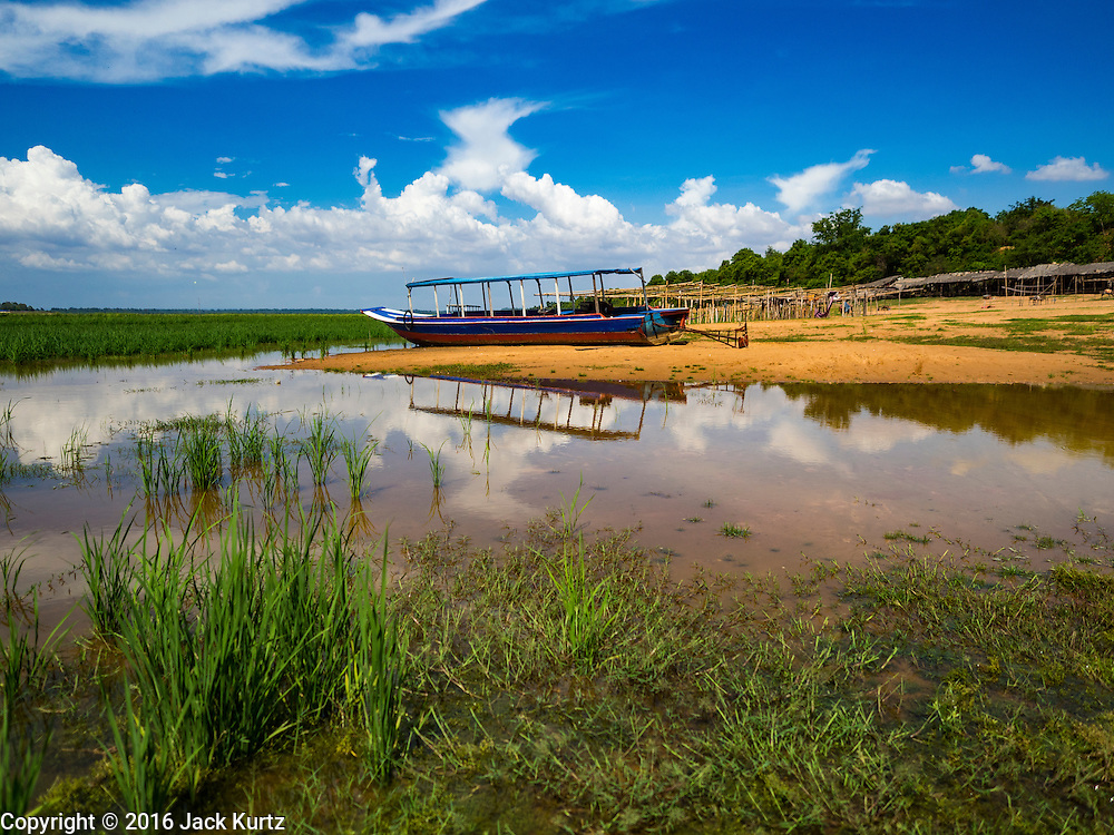 31 MAY 2016 - SIEM REAP, CAMBODIA: A tour boat beached in Sangkat Tuek Vil village on the West Baray near Siem Reap. The West Baray is an enormous reservoir by the Khmer empire in the 11th century. It is 8,000 metres long and 2,100 metres wide. It was built by hand and used to provide agricultural and domestic water to the empire based in the Angkor Wat complex. The Baray is still in use as a reservoir for farms in the area. It is empty for the first time in the living memory of the people who live around it. While the water level fluctuates enormously from the rainy season the dry season, it's virtually unheard for the Baray to be empty and it's been empty for at least a month. The boats that take tourists across the reservoir are beached and many of the small restaurants are closed until it floods again. Recent small rains have seen the water level rise a few inches but not enough to accommodate the boats.     PHOTO BY JACK KURTZ