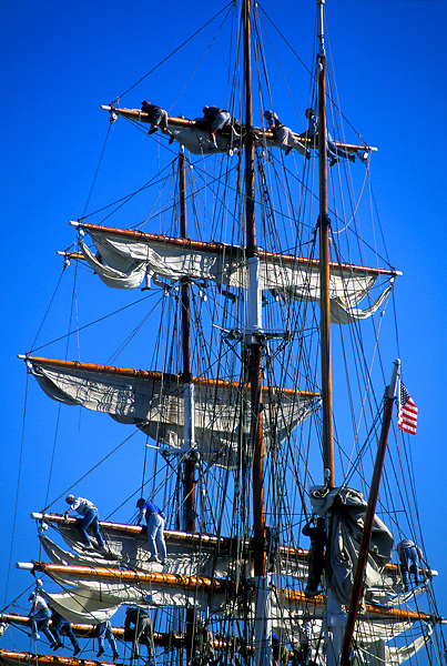 Men climbing and working on the rigging of the historic sailboat The Elissa in Galveston Texas