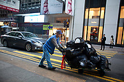 An old man pushes a cart loaded with rubbish bags through the streets of Central, the business district of Hong Kong. Many old people have to work as rubbish collectors to survive.  Hong Kong is one of the world's leading financial centres along side London and New York, it has one of the highest income per capita in the world as well the moste severe income inequality amongst advanced economies.  7 million people live on 1,104km square, making it Hong Kong the most vertical city in the world.
