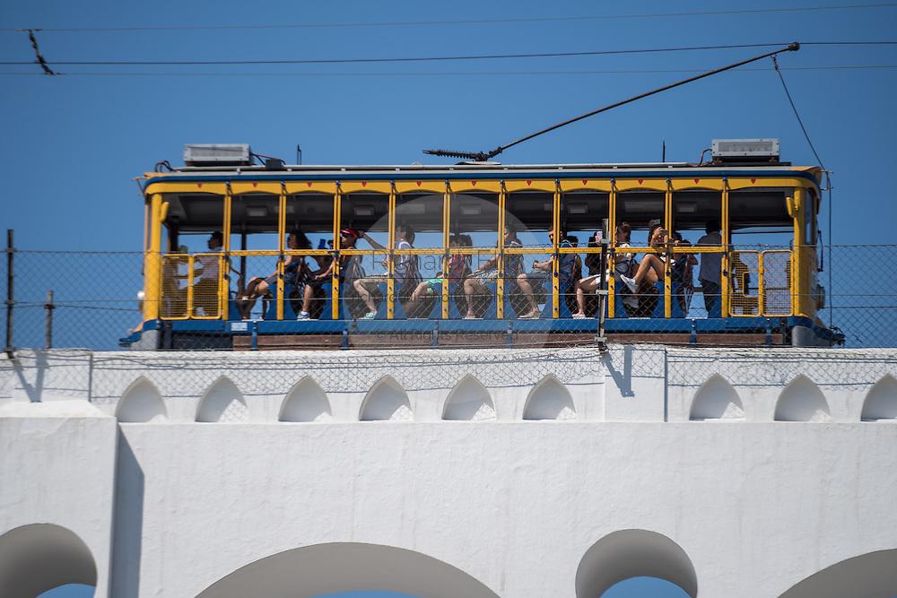 Tourists ride the Santa Teresa bonde historic tram line across the Carioca Aqueduct from the Santa Teresa neighborhood in Rio de Janeiro, Brazil.