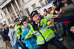 Westminster, October 9th 2014. A police officer tries to quell a scuffle in Trafalgar Square as scores of Kurds demonstrate against ISIS and demand that the UK and Turkey assist them in defending themselves against the Jihadist movement.