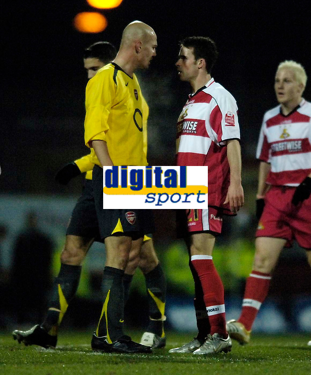 Photo: Jed Wee.<br /> Doncaster Rovers v Arsenal. Carling Cup. 21/12/2005.<br /> <br /> Doncaster's Michael McIndoe (R) squares up to Arsenal's Pascal Cygan.