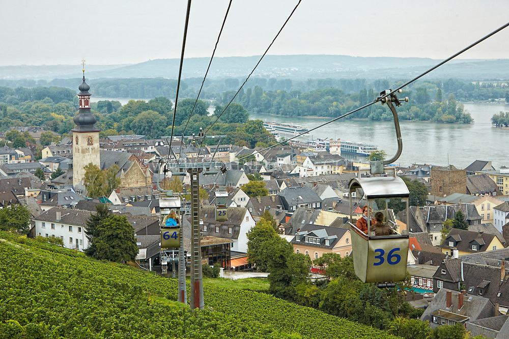 View of tourists, cable cars, Oberstrasse, St. Jakobus Church, vineyards, Market Square, and the Rhein, Rüdesheim, Germany.