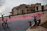 Protesters paint a new flag on an overpass in Banghazi on Feb. 25, 2011.