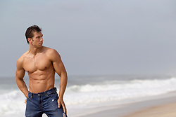 sexy man at the beach wearing jeans and no shirt
