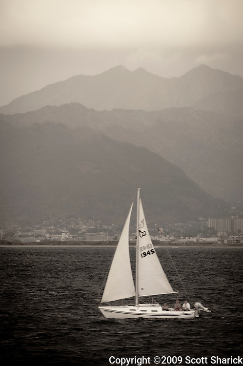 A small sailboat sails in front of the Koolau Mountains on Oahu.