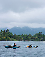 People use outrigger canoes and a mask and snorkel to fish in Nagada Harbor near the town of Madang, Papua New Guinea.