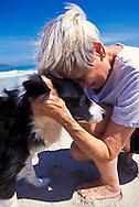 Mature age woman cuddling pet dog on beach, Kailua, Oahu, Hawaii *****Property Release available