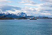 Hurtigruten ferry ship jagged mountains near Ornes, Nordland, Norway