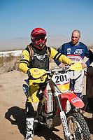 201x motorcycle rider Derek Duncan arrives at Honda pit #2 at race mile 70, 2012 San Felipe Baja 250, San Felipe, Baja California, Mexico.