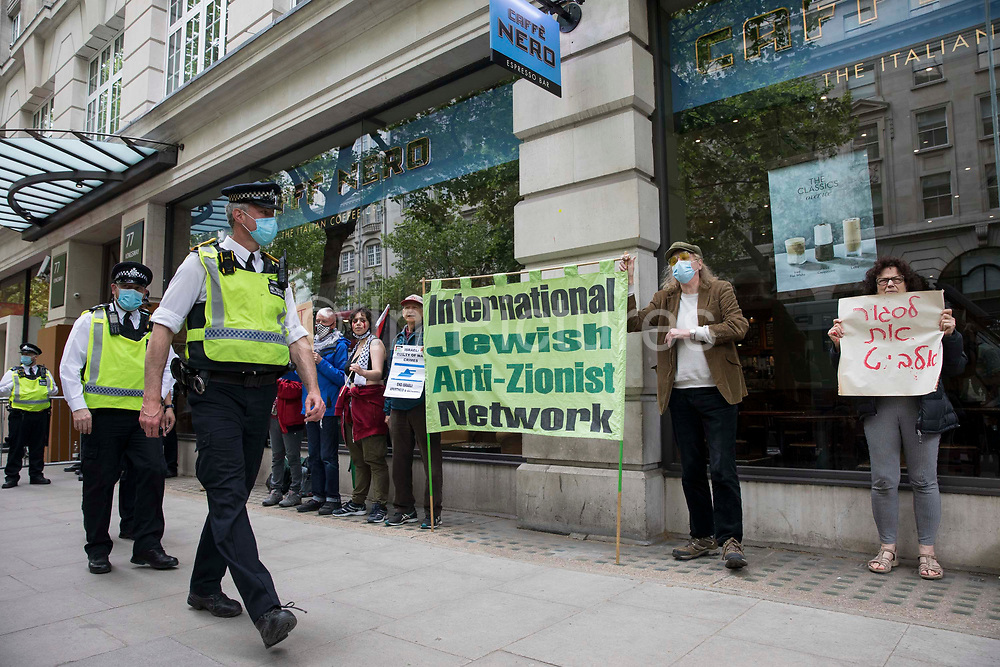 Metropolitan Police officers pass in front of activists from Palestine Action protesting outside the UK headquarters of Elbit Systems, an Israel-based company developing technologies used for military applications including drones, precision guidance, surveillance and intruder-detection systems, on 28th May 2021 in London, United Kingdom. Pro-Palestinian activists had organised the protest against Elbits presence in the UK and against British arms sales to and support for Israel.