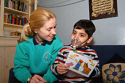A Children's Community Health Play Worker visits a sick  child; who due to his severe illness can't attend school; Children's Community Nursing Team; Bradford,