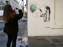 Edinburgh, Scotland, UK. 15 December 2020. Street art of Covid-19 vaccination by street artist  The Rebel Bear in Edinburgh is vandalised by anti vaccination protestor. Iain Masterton/Alamy Live News