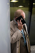 The cover of a smartphone obscures the face of a businessman in the City of London.