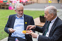 © Licensed to London News Pictures . 24/09/2016 . Liverpool , UK . JEREMY CORBYN and FRANK FIELD (r) eat pizza breads Corbyn made during a visit to Beaconsfield Community House in Birkenhead , following his victory declaration . The centre provides clothes and food that would otherwise be destined for waste from supermarkets , to local residents in need . Photo credit : Joel Goodman/LNP