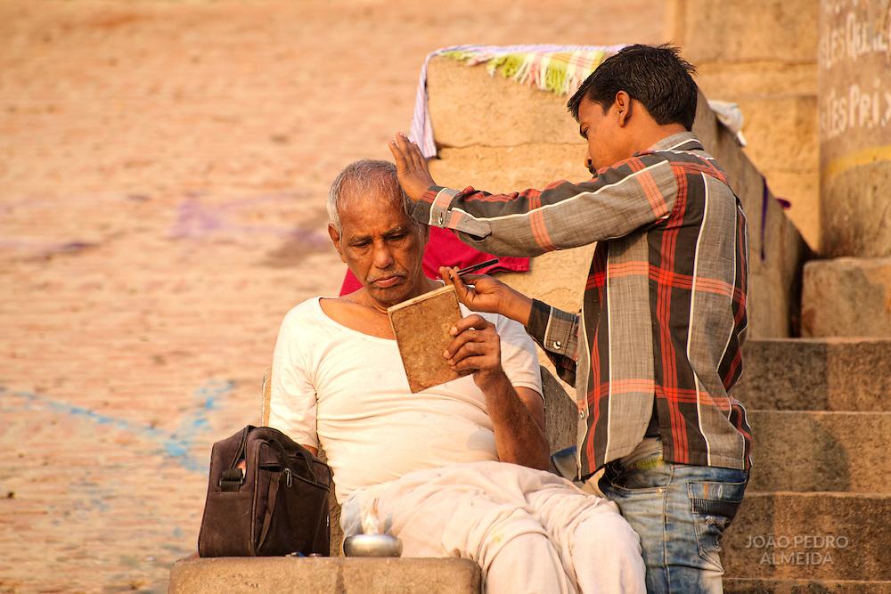Man looking at mirror in a street barber at Varanasi