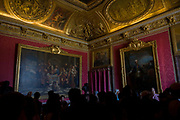 "Tourists crowd in the Salon de Mars in the King's Grand Apartment, Versaille, Paris. The choice of this military theme which inspired all the decoration of the salon can be explained by the fact that this large room was originally meant to serve as the guard room for the parade apartment. It was later reserved, at evening soirees, for music and dancing, so that it was commonly known as the ""ballroom"". The court ballets were strictly regulated and required many rehearsals; the princes took part in them, sometimes mixed in with professional dancers. The Palace of Versailles or simply Versailles, is a royal château in Versailles in the Île-de-France region of France. In French it is the Château de Versailles."